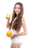 La ragazza si è vestita in un succo d'arancia bevente della camicia bianca contro un wh Fotografia Stock Libera da Diritti