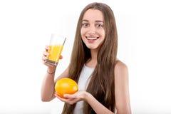 La ragazza si è vestita in un succo d'arancia bevente della camicia bianca contro un wh Immagine Stock
