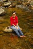 La ragazza si distende in flusso dopo l'escursione Fotografie Stock