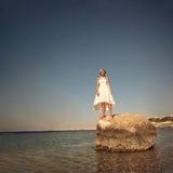 La ragazza si leva in piedi sulla pietra Immagine Stock