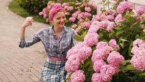 La ragazza si preoccupa per i fiori rosa Germogli fertili incredibile bei dei fiori rosa Fiori d'innaffiatura della donna Fiori l archivi video