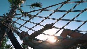 La ragazza si rilassa in un'amaca vicino alle palme archivi video