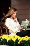 La ragazza si siede ad una tabella Immagine Stock