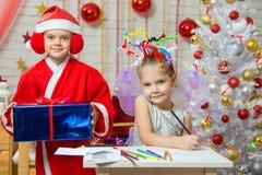 La ragazza si siede ad una tavola con i fuochi d'artificio sulla testa, Santa Claus è un piccolo indietro con un regalo Fotografia Stock Libera da Diritti