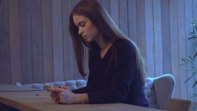 La ragazza si siede ad uno scrittorio e ad esaminare il telefono video d archivio