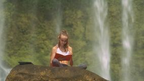 La ragazza si siede al taccuino sulla scogliera in parco nazionale stock footage