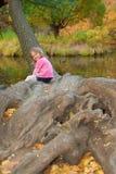 La ragazza si siede in albero e sorride Immagine Stock