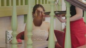 La ragazza si siede alla tavola stock footage