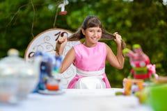 La ragazza si siede alla tavola e tira i suoi capelli Alice dentro Fotografie Stock Libere da Diritti