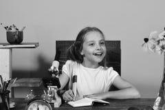 La ragazza si siede allo scrittorio con il microscopio e la sveglia rossa Fotografia Stock Libera da Diritti