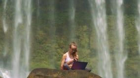 La ragazza si siede con il computer portatile ed il telefono sulla scogliera all'acqua stock footage