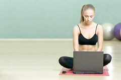 La ragazza si siede con il computer portatile in ginnastica di sport fotografie stock