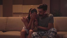 La ragazza si siede con il tipo sul sofà Sta gridando Fronte delle coperture della donna con le mani e stringere con la testa del archivi video