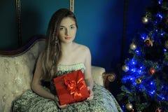 La ragazza si siede con una scatola rossa fotografia stock