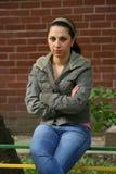 La ragazza si siede ed attendere esterna. Fotografie Stock