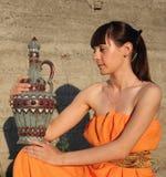 La ragazza si siede ed ha controllo sopra una brocca Fotografia Stock