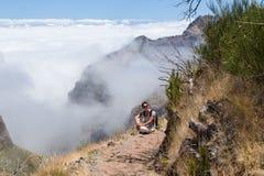 La ragazza si siede ha un resto su una pista turistica nelle montagne di Fotografia Stock Libera da Diritti