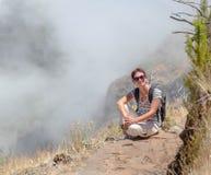 La ragazza si siede ha un resto sul punto della rottura fra le nuvole nella t Fotografia Stock Libera da Diritti