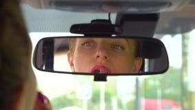 La ragazza si siede in labbra dei coveres e dell'automobile con rossetto Guarda in specchio La ragazza mette parecchi strati di c video d archivio