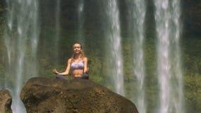 La ragazza si siede in Lotus Pose sulla roccia di Brown dalla cascata archivi video