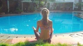 La ragazza si siede nella posa Lotus di yoga dalla vista della parte della piscina archivi video