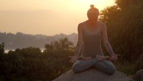 La ragazza si siede in padmasana su roccia rotonda al movimento lento dell'alba archivi video