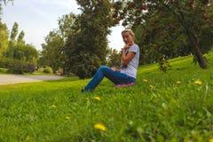 La ragazza si siede in parco sull'erba Fotografie Stock Libere da Diritti