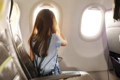 La ragazza si siede in salone l'aereo Fotografia Stock