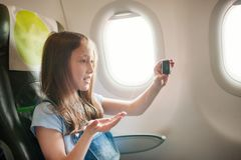 La ragazza si siede in salone l'aereo su seduta del passeggero Fotografia Stock Libera da Diritti