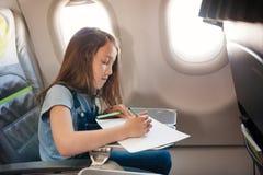 La ragazza si siede in salone l'aereo su seduta del passeggero immagini stock