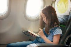 La ragazza si siede in salone l'aereo su seduta del passeggero fotografia stock