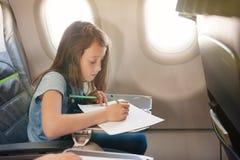 La ragazza si siede in salone l'aereo su seduta del passeggero immagine stock