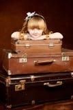 La ragazza si siede su bagaglio d'annata immagini stock libere da diritti