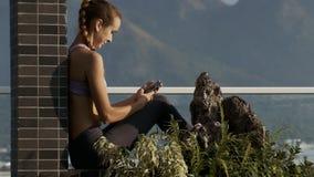 La ragazza si siede su Internet delle spume del terrazzo su Smartphone video d archivio
