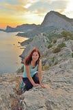 La ragazza si siede su un'alta collina dal mare al tramonto Fotografia Stock