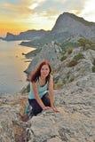 La ragazza si siede su un'alta collina dal mare al tramonto Immagini Stock Libere da Diritti