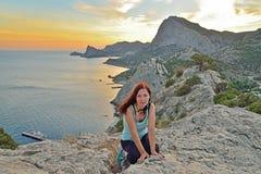 La ragazza si siede su un'alta collina dal mare al tramonto Fotografia Stock Libera da Diritti