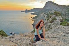 La ragazza si siede su un'alta collina dal mare al tramonto Immagine Stock Libera da Diritti