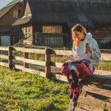 La ragazza si siede su un banco di legno nelle montagne in natura, legge un libro, beve il tè caldo da una termo tazza Concetti c fotografia stock
