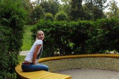 La ragazza si siede su un banco di parco Fotografia Stock Libera da Diritti