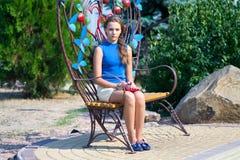 La ragazza si siede su un banco di parco calzato Fotografia Stock Libera da Diritti