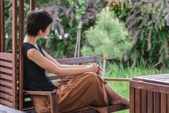 La ragazza si siede su un banco ed esamina meditatamente la distanza distendasi Fotografie Stock