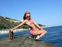 La ragazza si siede su un molo Fotografia Stock