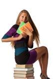 La ragazza si siede su un mucchio dei libri Fotografie Stock Libere da Diritti