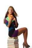 La ragazza si siede su un mucchio dei libri Fotografie Stock