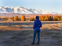 La ragazza si siede sui cappotti e gode dell'alba nelle montagne fotografia stock