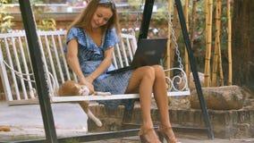 La ragazza si siede sui giochi delle oscillazioni del banco di parco con il gatto rosso archivi video