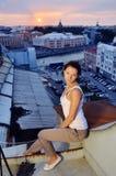 La ragazza si siede sui tetti Immagini Stock