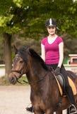 La ragazza si siede sul suo cavallino Fotografie Stock