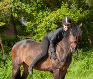 La ragazza si siede sul suo cavallino Fotografie Stock Libere da Diritti